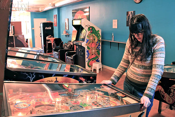 Girl playing pinball.