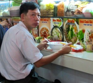 Vietnamese man eating at the market