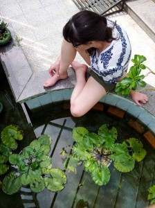 Sara sits by the pond and the water lilies.