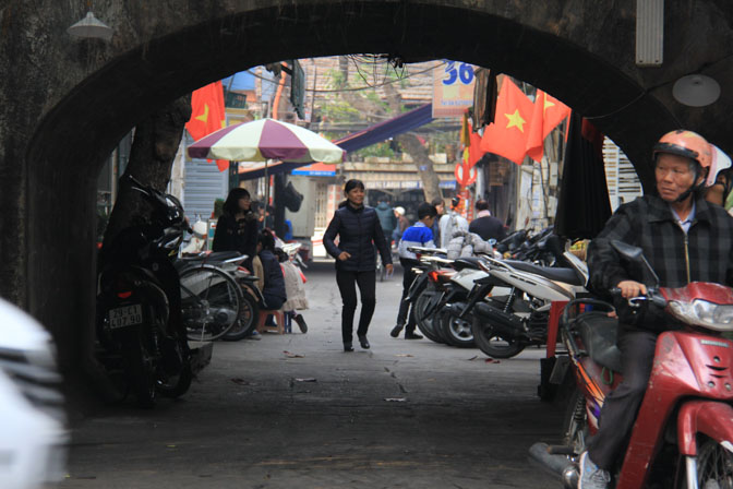 A woman walks under a train bridge in Hanoi, Vietnam
