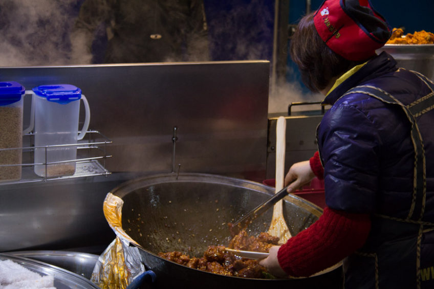 A cook coats some chicken in sweet and spicy sauce